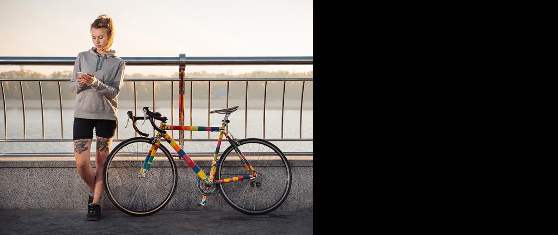 blondwłosa dziewczyna z tatuażami stoi przy kolorowym rowerze z ostrym kołem